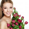Beautiful smiling blonde woman with flowers — Stock Photo
