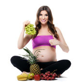 Smiling pregnant woman with fruits — Stock Photo