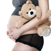 Belly of a pregnant woman with a plush toy — Stock Photo