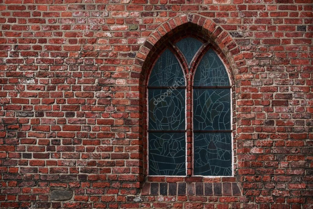 Muro di mattoni gotici con una finestra, una finestra di vetro ...