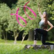 Beautiful gymnast exerciser in nature — Stock Photo