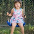 Laughing little girl on a swing — Stockfoto