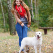 Beautiful woman walking with her dog in the forest  — Photo