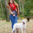 Beautiful woman walking with her dog in the forest  — Stock fotografie