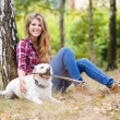 Beautiful womwalking with her dog in forest — Stock Photo #32321043