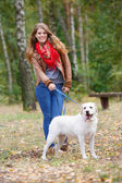Beautiful woman walking with her dog in the forest — Stock Photo