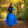 A beautiful woman in a blue dress in autumn park — Stock Photo