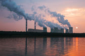 The smoke from the chimneys of a power plant at sunset — Stock Photo