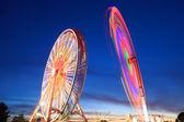 Amusement park at dusk - Ferris wheel in motion — Stock Photo