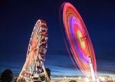Amusement park at night - ferris wheel in motion — Stock Photo