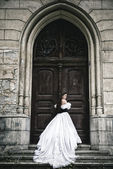 Mysterious woman in Victorian dress with old doors — Stock Photo