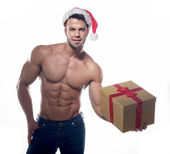 Muscular, sexy santa claus with gift — Stock Photo