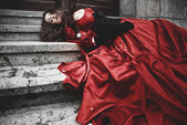 Lying and bleeding woman in a red Victorian dress — Stock Photo