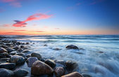 Sunset over the Baltic sea. The pebbly beach in Rozewie — Stock Photo