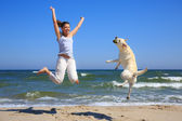 Woman and dog breed Labrador jumping on the beach — Stock Photo