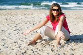 Gesticulating woman on the beach in sunglasses — Stock Photo