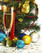 Festive image of a glass of champagne, candles and Christmas tree — Stock Photo