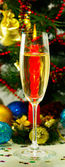 Image of wineglass with champagne  against the  beautiful Christmas tree and candles — Stock Photo