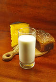 Image of a glass of milk, bread on the board, spike and cheese — Stock Photo