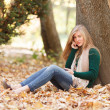 Woman talking on the phone in autumn park — Stock Photo