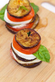 Eggplant with mozzarella cheese, tomatoes and basil — Stock Photo