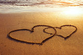 Two hearts on the beach — Stockfoto