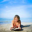 Reading on the beach - Stock Photo
