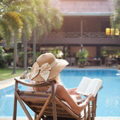 Woman reading book in deck chair — Stock Photo