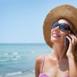 Woman with mobile phone on the beach — Stock Photo