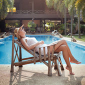 Woman sleeping near the swimming pool — Stock Photo
