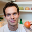 Stock Photo: Young mholding apple near refrigerator