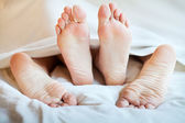 Сouple feets in bed under a coverlet — Stock Photo