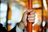 Hand holds handrail in public transport — Stock fotografie