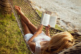 Woman lying in a hammock and reading book — Stock Photo