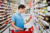 Guy chooses groceries in supermarket — Stockfoto