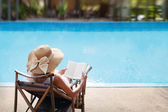 Woman relaxing near swimming pool — Stockfoto