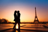 Couple kissing on Eiffel Tower background — Stockfoto