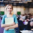 Young female student holding file and looking at the camera — Stock Photo #47104497