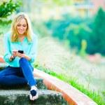 glada leende flicka skriver ett meddelande — Stockfoto