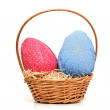 Easter eggs and wicker basket - Stock Photo
