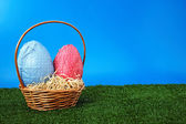 Easter eggs and wicker basket on garden — Stock Photo