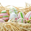 Stockfoto: Easter eggs into nest from bottom