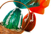 Cellophane Easter eggs in a basket — Stock Photo