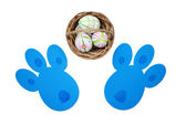Easter eggs in a basket and bunny tracks top view — Stockfoto