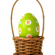 Green Easter egg into a basket — Stock Photo