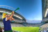 Brazilian fan at stadium playing vuvuzela — Stock Photo