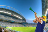 Brazilian fan at stadium playing vuvuzela — Stock Photo