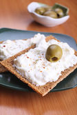 Snack of rye crisps witn spicy cream cheese and olives — Stock Photo