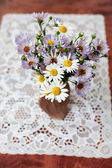 Camomile and aster bouquet in a vase on a table — Stock Photo