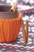 керамическая чашка в вязаной держатель с корицей — Стоковое фото